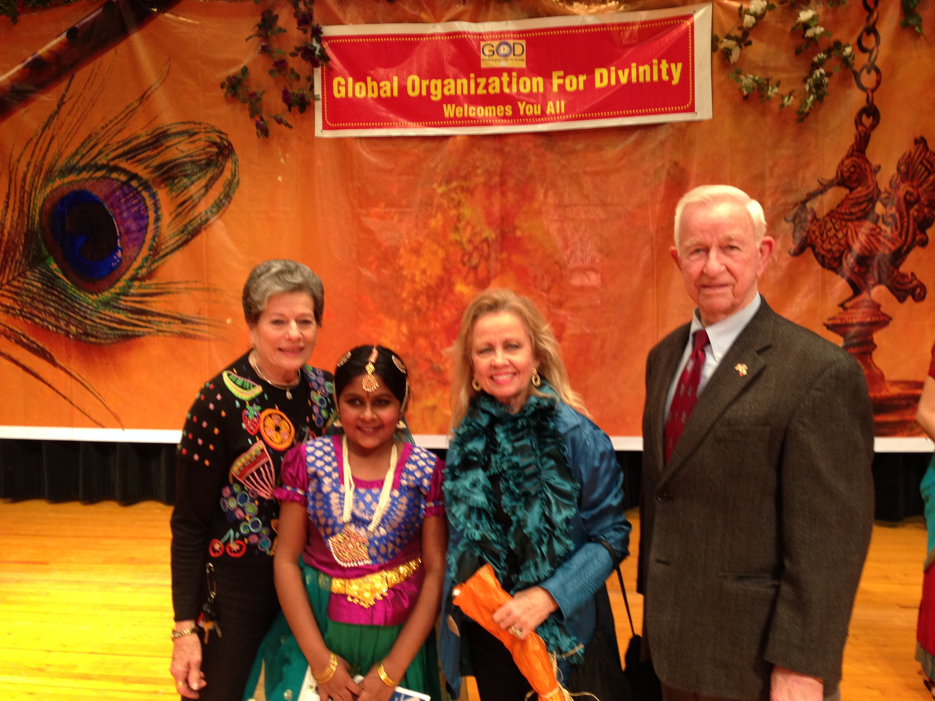 Posed photo of the mayor, an older man in a suit and tie, a woman and a young girl dressed in colorful garb
